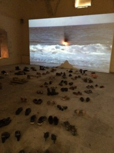 Installation av Marios Spiliopoulos: flyktingars skor vid Medelhavets vågor. Från utställningen Guds 700 namn.