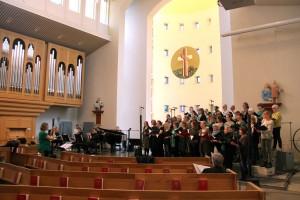 Kören - fina med sina gröna attiraljer - fyller Lundby nya kyrka med klang och jubel under genrepet.