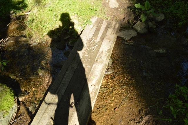 Skuggan av två pilgrimer, en till fots och en i bärstol på ryggen.