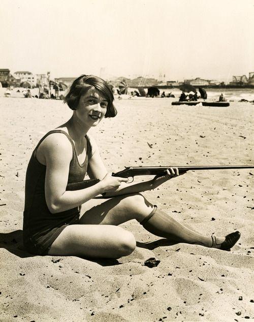 Väldigt blandad bild. Kvinna med gevär på sandstrand. Om man vill kanske man kan få den till att handla om öknen och prövningen?