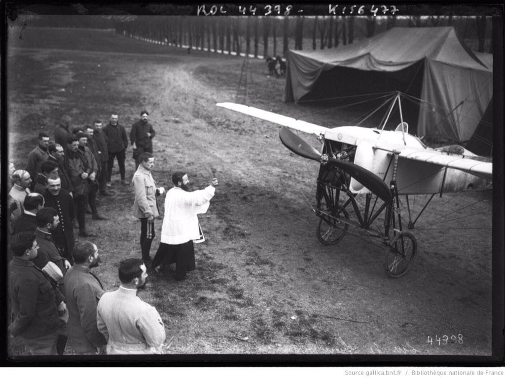 Präst som välsignar ett flygplan. Hoppas verkligen inte att det är ett krigsplan för då visar de inte prov på värst mycket andlig klarsyn.