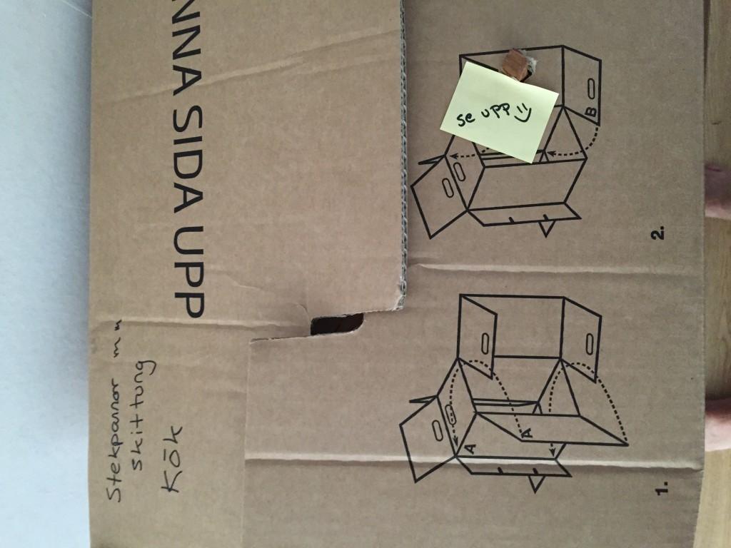 Bild på flyttkartong med hål i. Bildtext: När flyttkartongen trots envisa försök fortfarande är för liten så får en se till att göra lite kreativa modifieringar (läs: hål). Foto och fotägare: Ulrika Wippel