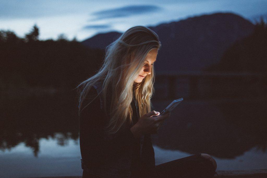 Kvinna läser på mobiltelefon utomhus på kvällen vid en sjö