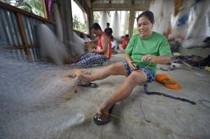 Jeanette Quilitano tillverkar nytt fiskenät på ön Jinamoc. Foto: Paul Jeffrey/IKON
