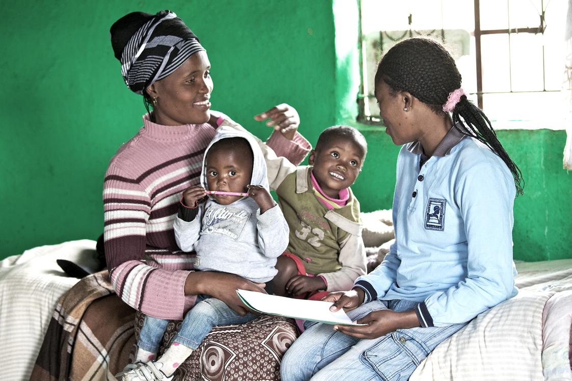 Nosiphela Luthuli diskuterar hälsa och näring med mentormamma Nozibele Chopele. Nosiphelas barn Bayanda och Asphile är med och lyssnar. Foto: Simon Stanford /IKON