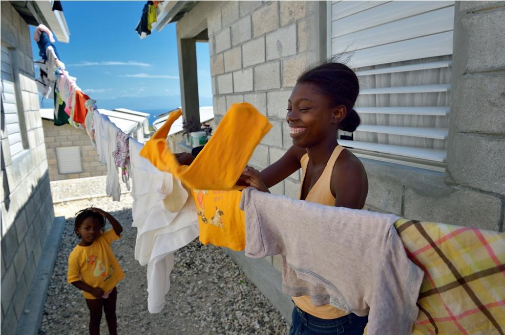 En kvinna hänger tvätt i en av de så kallade modellbyarna som Svenska kyrkan har varit med och finansierat. 150 familjer bor i byn.  Foto: Paul Jeffrey /IKON