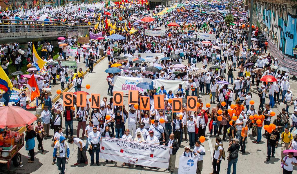 Konferensdeltagarna demonstrerar tillsammans med tusentals andra i centrala Bogota för att hedra minnena av krigets offer, på krigsoffrens dag den 9 April. Foto:  Anna Vogt /Justapaz