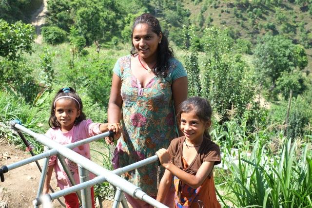 Mrs Dinarath med sina barn vid vattentanken som hon nu har runt husknuten. Foto: Peter Butor