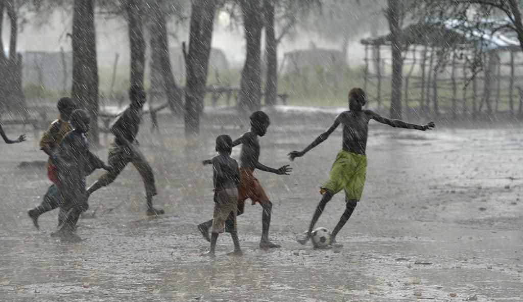 Några barn spelar fotboll i regnet i flyktinglägret Doro i Sydsudan. Barn har en unik förmåga att klara av de extrema förhållanden som de tvingas leva under i sin vardag på flykt. Vi vil göra allt för att stödja dem. Foto: Paul Jeffrey /ACT